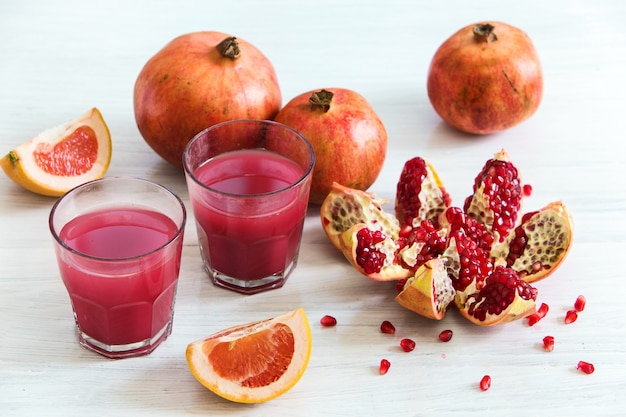 Pomegranate liqueur in glasses and whore pomegranates on wooden table
