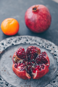 Pomegranate in plate with mandarin on dark