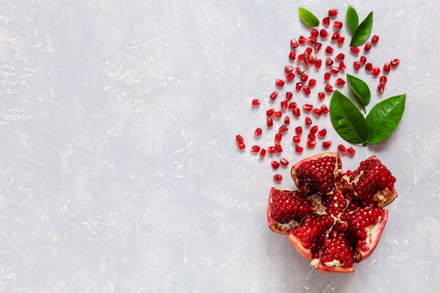 Pomegranate  and pomegranate seeds on light concrete background.