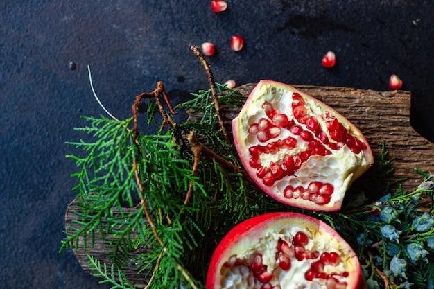 テーブルと緑のクリスマスツリーの小枝にザクロの赤い果実の甘い