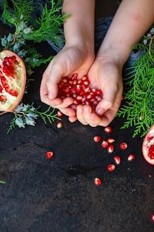 Гранатовый красный фрукт сладкий на столе и веточка зеленой елки