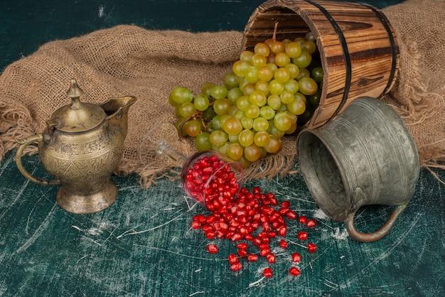 Семена граната и ведро винограда на мраморном столе с вазой и чайником.