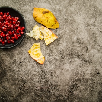 Pomegranate seeds and peel on stained background