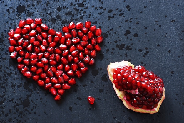 Pomegranate seeds are stacked in the form of a heart on a black surface.