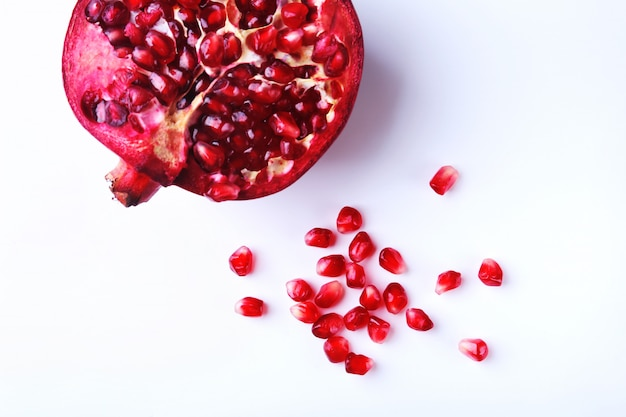 Pomegranate seeds and beautiful ripe pomegranate on white