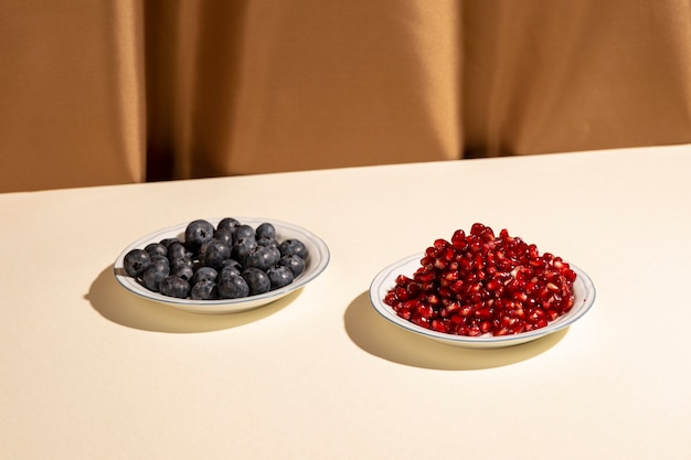 Pomegranate seeds and blueberries on plate over white table near brown curtain