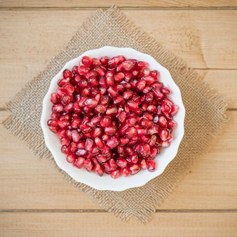 Pomegranate seeds in a bowl on a wooden table.