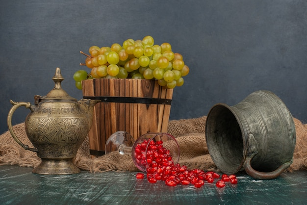 Pomegranate seeds and bucket of grapes on marble table with vase and teapot.