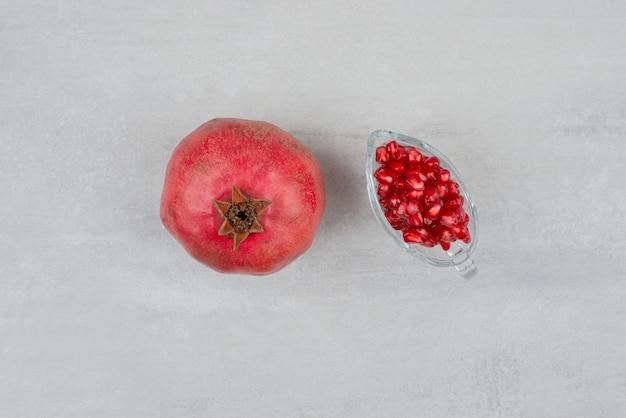 Семена граната в стекле и гранате на белой поверхности.
