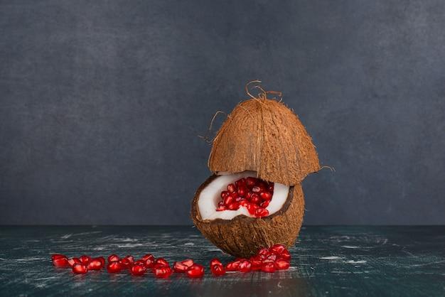 大理石の表面のココナッツの中のザクロの種子