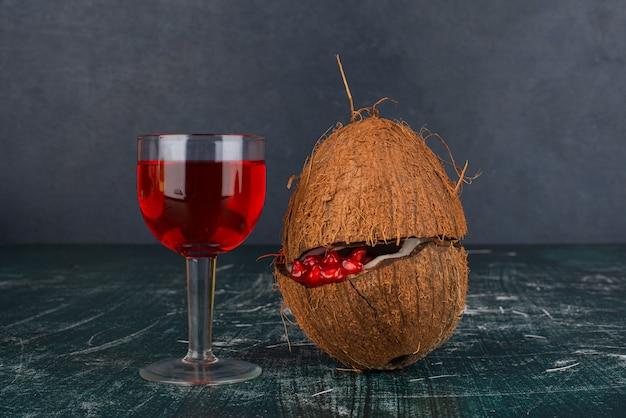 Semi di melograno all'interno di cocco e bicchiere di vino rosso sulla superficie in marmo.