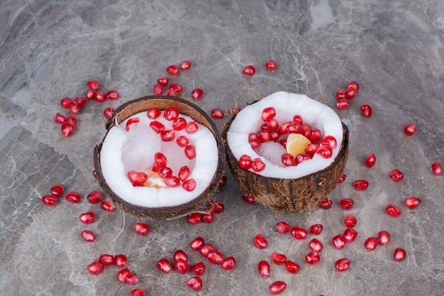 코코넛 내부와 표면에 석류 씨앗.