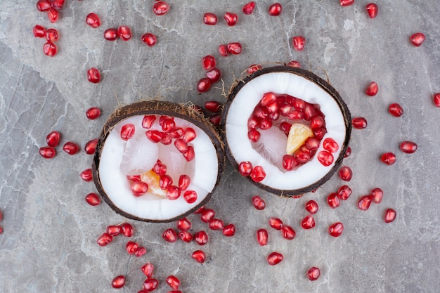 Pomegranate seeds inside coconuts and on surface.