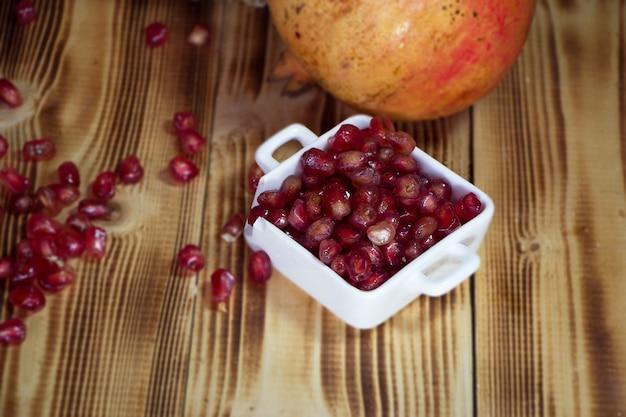 The pomegranate seeds put in ceramic cup,on wooden timber board