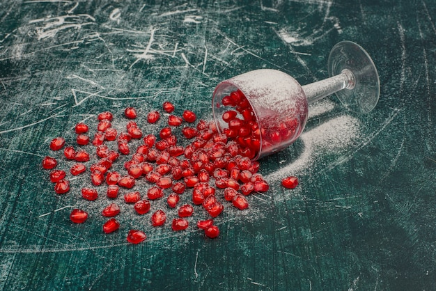 Pomegranate seeds scattered on marble surface.
