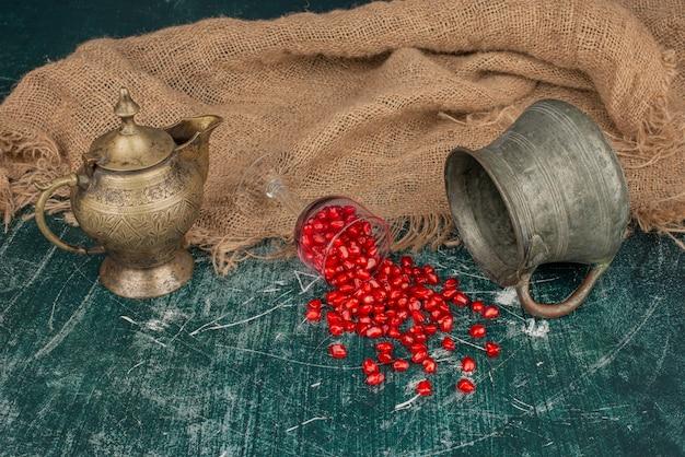 Семена граната разбросаны на мраморном столе с вазой и чайником.