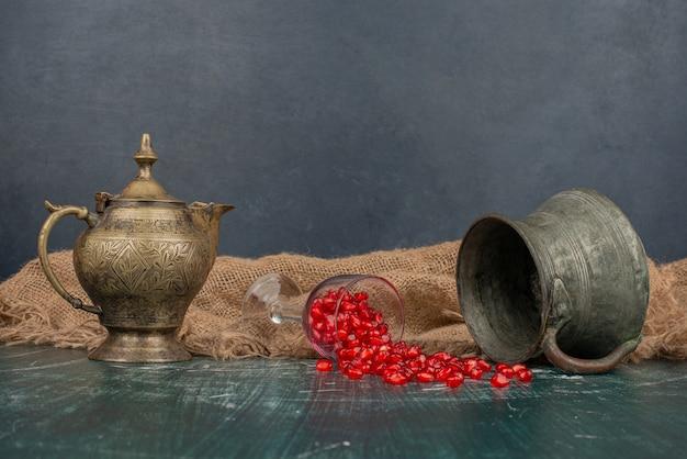 석류 씨앗은 꽃병과 주전자가있는 대리석 테이블에 흩어져 있습니다.