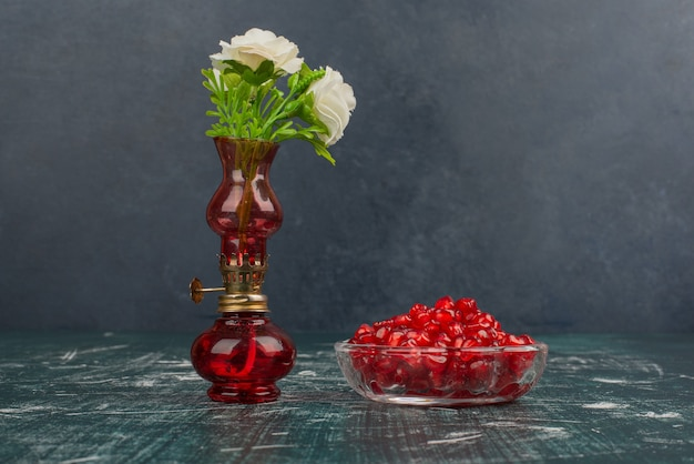 Pomegranate seeds and white flowers in vase.