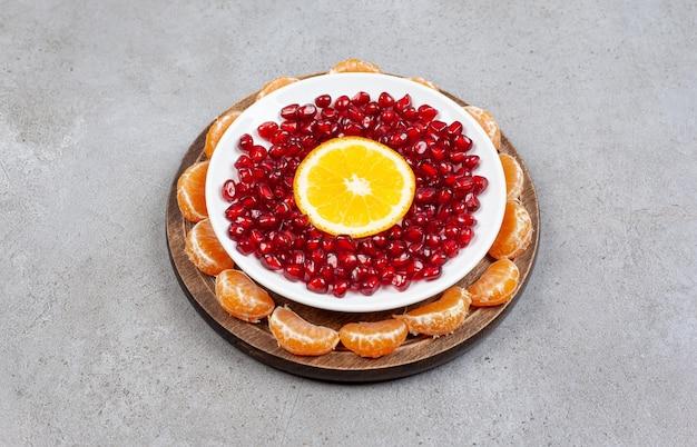 Семена граната с долькой апельсина на белой тарелке над деревянной доской с дольками мандарина.