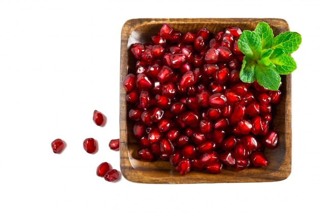 Pomegranate seeds in wooden bowl isolated on white background.