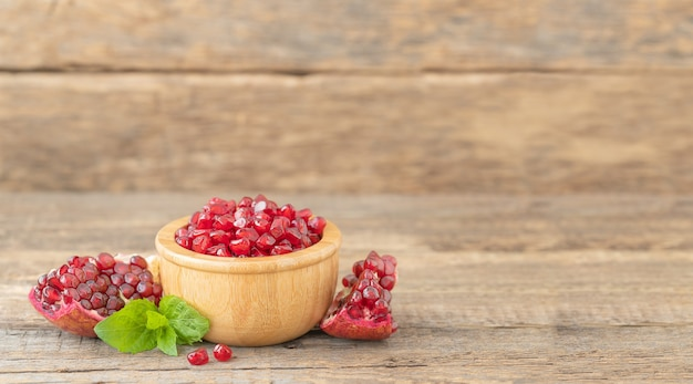 Pomegranate seeds in a wooden bowl and slicces of pomegranate on a wooden surface