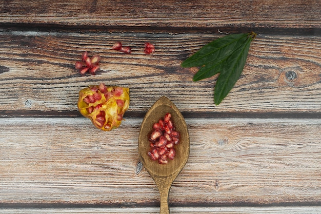 Pomegranate on table with wooden spoon