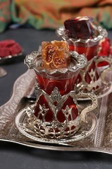 暗い背景、クローズアップ、垂直形式の金属トレイにザクロ茶とトルコ菓子