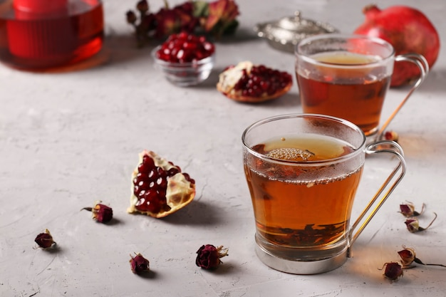 Pomegranate tea in two transparent cups on a gray concrete background, warming wellness drink, space for text