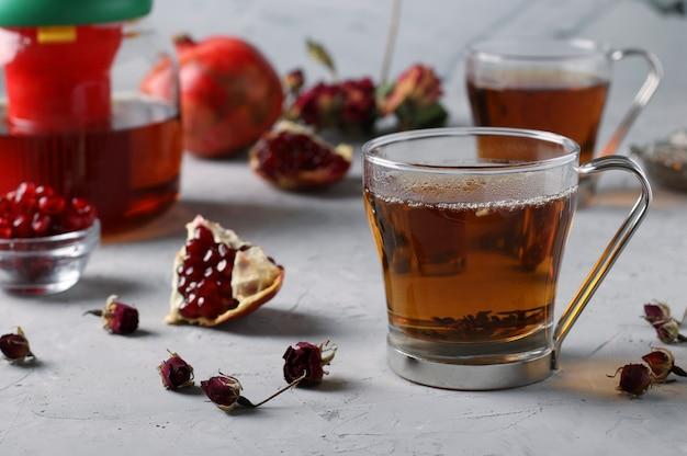 Pomegranate tea with lemon and cinnamon in two transparent cups on a gray concrete surface, warming wellness drink