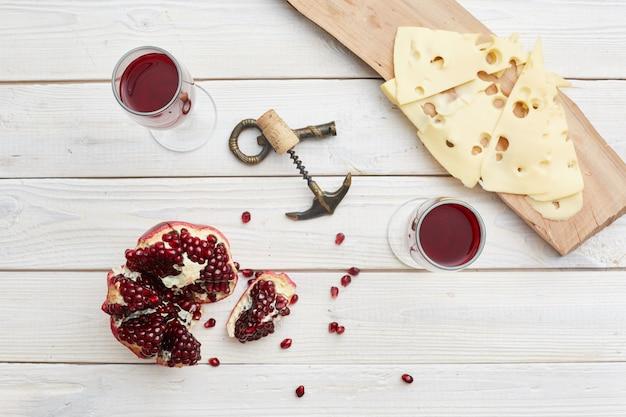 白い木製のテーブルでザクロワイン。上面図。チーズ、コルク抜き
