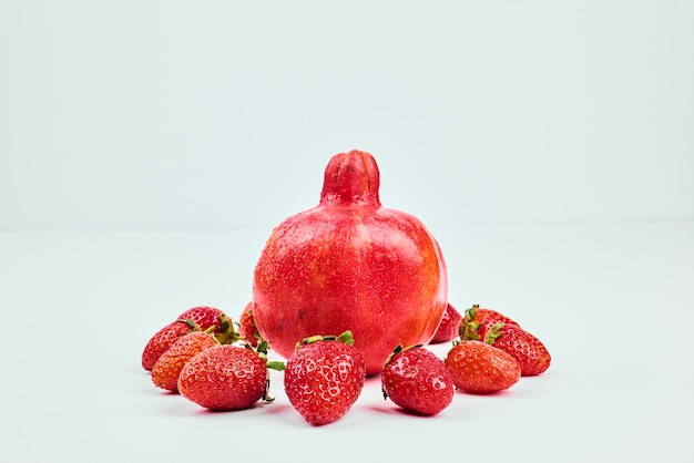 A pomegranate with strawberries on white isolated.