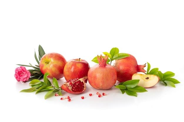 Гранаты и красные яблоки на белом фоне, традиционная еда еврейского нового года - рош ха-шана.