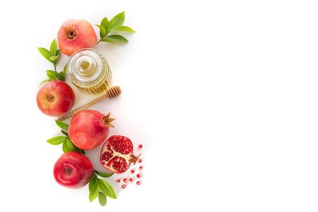 Гранаты, яблоки и мед на белом фоне, традиционная еда еврейского нового года - рош ха-шана. вид сверху. скопируйте космический фон