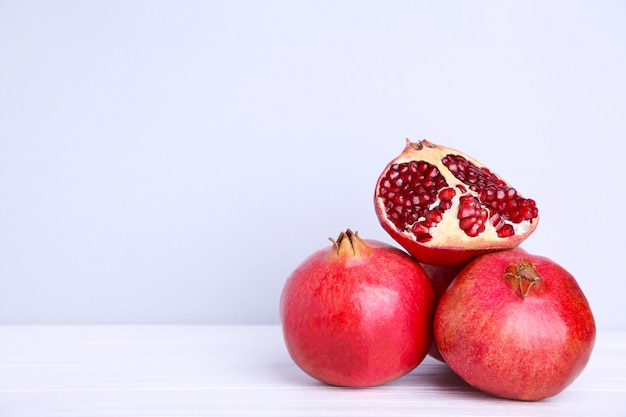 Pomegranates and half of ripe pomegranate on a grey background