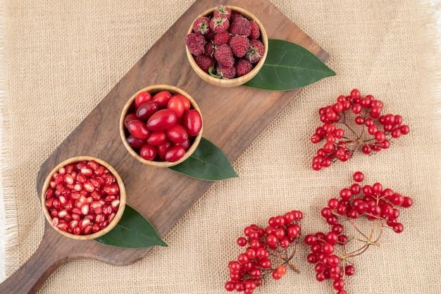 Pomegranates. hips and raspberries in wooden bowls with clusters of redcurrant on textile background. high quality photo