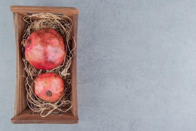 Гранаты в деревянной корзине на мраморе Бесплатные Фотографии