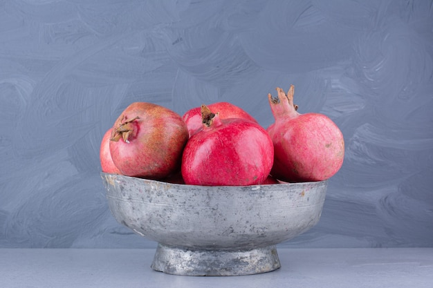 Melograni in un vaso di metallo su sfondo marmo.