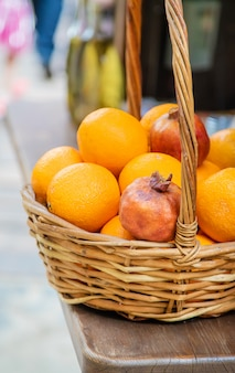 Pomegranates and oranges are sold in the market.