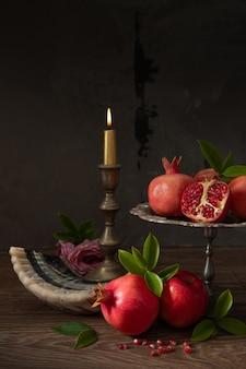 Гранаты, красные яблоки, шофар (рог) и горящая свеча, еврейский новый год - рош ха-шана