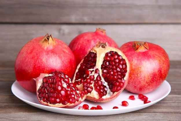 Pomegranates on white plate on a brown background
