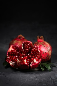 Pomegranates with leaves, on a wooden table, rustic style