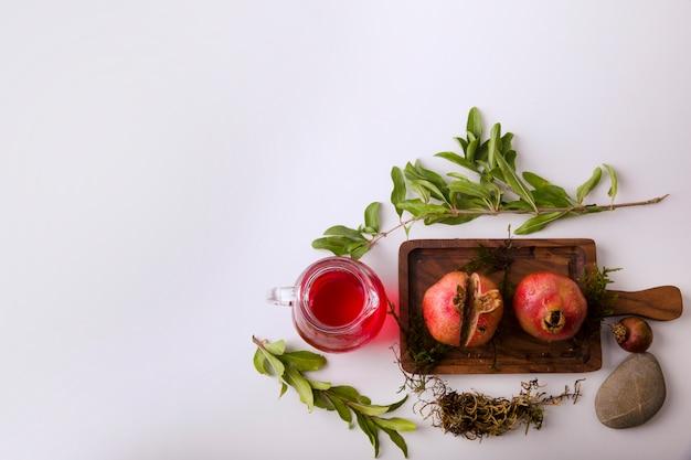 Melograni con salsa rossa e succo su una tavola di legno, vista dall'alto
