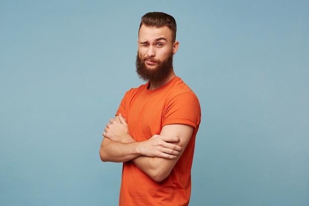 Напыщенный, высокомерный бородатый парень изолирован на синем, смотрит небрежно и презрительно, полуобернувшись со скрещенными руками