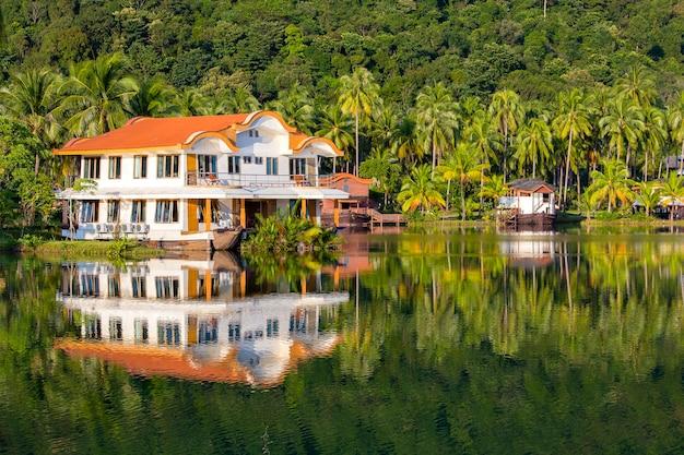 태국의 녹색 코코넛 야자수와 호수 물이있는 아름다운 열대 장소 앞의 연못