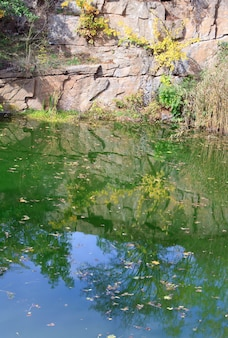 Pond water surface with reflection of colorful trees  and rocky lakeside in autumn park