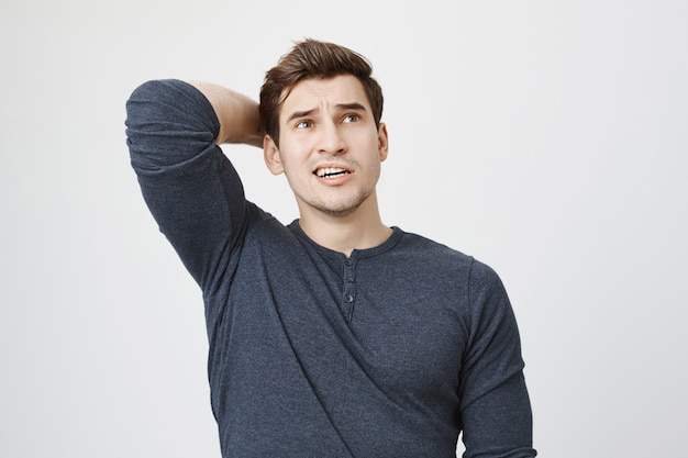Pondering concerned man thinking, scratch back of head indecisive