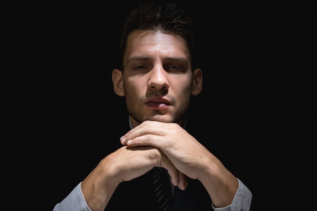 Pondering man in black suit with hands on chin in dark shadow