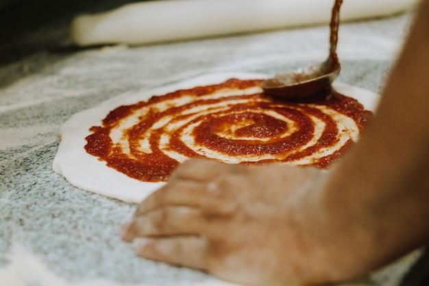 Poniendo tomate en masa de pizza