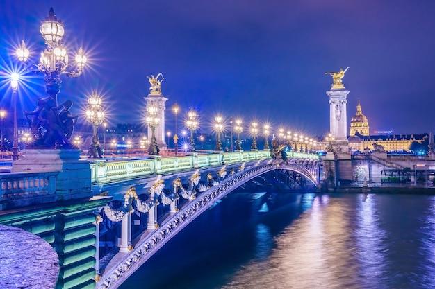 Мост pont alexandre iii через реку сена и отель инвалидов в сумерках