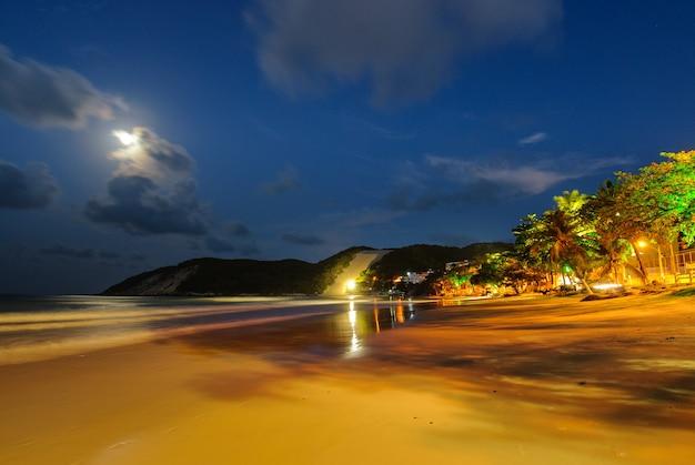 Пляж понта-негра на фоне морро-ду-карека в ночь полнолуния, натал, риу-гранди-ду-норти, бразилия, 19 февраля 2008 года.